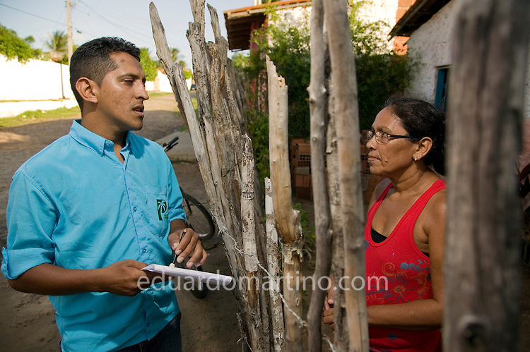 "When Palmas Bank is asked for money in credit, one of their ways to evaluate the reputation of the client is to visit the client's neighbours and ask their opinion. Here a member of staff from Palmas Bank, Francisco Gilvanilson Holanda Ibiapino, talks to ""Garota Fashion"" Maria da Conceição Holanda Granja's neighbour, Maria Lucia da Silva Nascimento..Conjunto Palmeiras, Fortaleza, Ceara, Brazil.Photo: Eduardo Martino / Documentography"