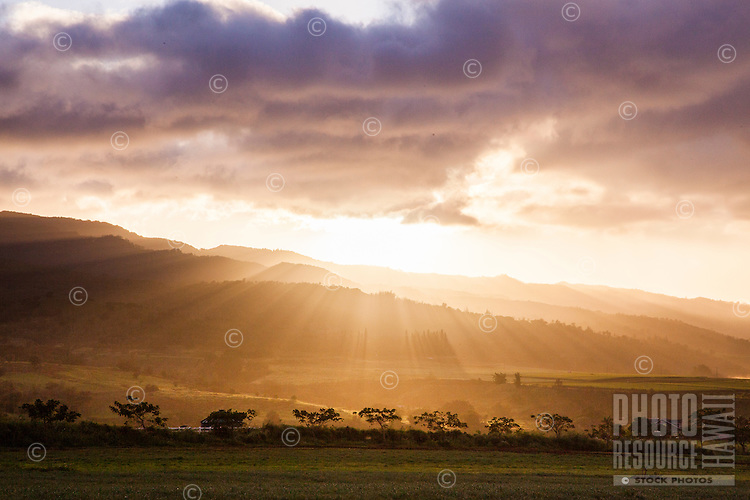 Beautiful sunset behind mountains with sun rays hitting the lush hills and landscape of Oahu.
