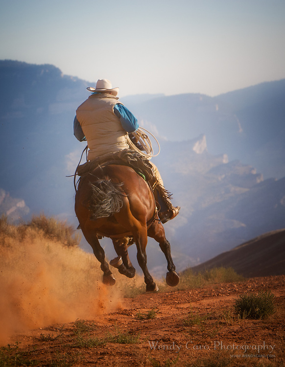 Rear view of Wyoming cowboy galloping towards a mountain escarpment, foothills of the Bighorn Mountains