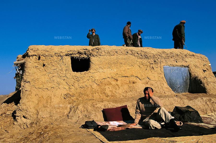 Afghanistan. Takhar. Dasht-e Qal'eh. November 2000. Seated with his bodyguards in front of Shafagh position's bunker, Commandant Massoud prepares the offensive. <br /> <br /> <br /> Afghanistan. Takhar. Dasht-e Ghala. Novembre 2000.<br /> Massoud assis devant le bunker de la position de Shafagh, avec ses gardes du corps, pr&Egrave;parant l'offensive.