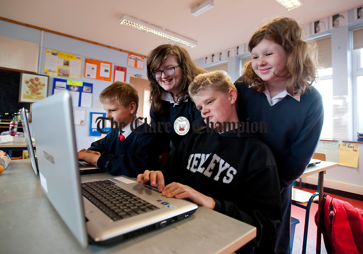 Oisín Keane, Anna and Nathan Fahy and Orla O' Dea on the laptops at New Quay National School. Photograph by Declan Monaghan