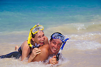 Couple wearing snorkel gear have fun at the shore at a beautiful beach on Oahu.