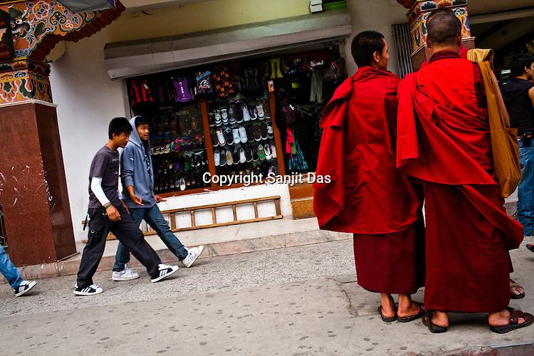 Bhutanese youngsters walk past Buddhist monks at the main market in Thimphu, Bhutan. Photo: Sanjit Das/Panos