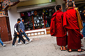 Bhutanese youngsters walk past Buddhist monks at the main market in Thimphu, Bhutan. Photo: Sanjit Das/Panos
