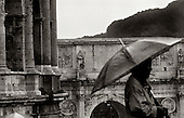 A man walks past the coliseum in the rain in Rome, Italy. photo by jane therese