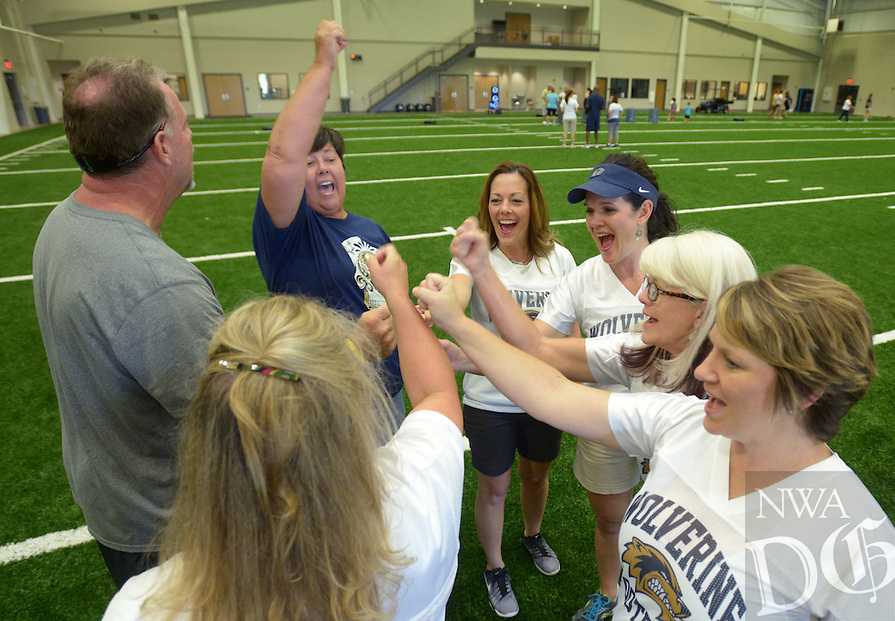 NWA Democrat-Gazette/BEN GOFF @NWABENGOFF<br /> Football moms join Bentonville West receivers coach Kyle Marr in a huddle after learning the basics of catching a pass on Sunday Aug. 21, 2016 during Wolverine Helmets and Heels at Bentonville West High School in Centerton. The event was an oportunity for mothers and other female relatives of Bentonville West football players to meet coaching staff and learn more about the game.