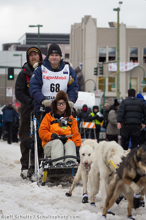 Timothy Hunt and team leave the ceremonial start line with an Iditarider at 4th Avenue and D street in downtown Anchorage, Alaska during the 2015 Iditarod race. Photo by Jim Kohl/IditarodPhotos.com