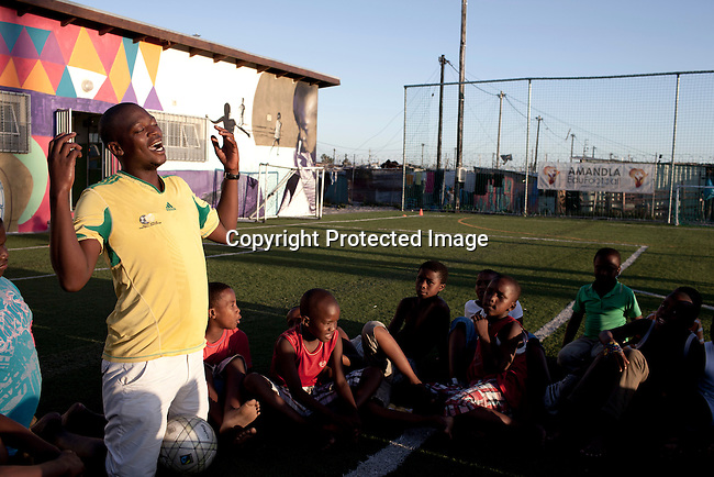 Khayelitsha, South Africa March 11, 2013: Malvin Maras, a Senior leader, holds a skills training session at Amandla EduFootball which was founded by Jakob Schlichti and Florian Zech in the field in Khayelitsha a poor township outside Cape Town, South Africa. They use football to initiate, support educational projects for youth in the township. The program keep children busy and it decreases the risk of them joining gang, criminal activity or teenage pregnancy. The crime level has decreased substantially in the area since the program was created in 2006. (Photo by: Per-Anders Pettersson)