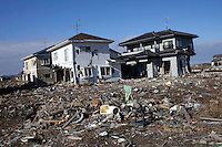 OMAGARIHAMA, JAPAN - DECEMBER 5: A few houses still stands next to a wiped out residential area on December 5, 2011, in the port of Omagarihama, Japan. The small town was almost wiped off the map during the tsunami Northeastern Japan's coastline was struck by an earthquake measuring 9.0 on the Richter scale and a Tsunami on March 11, 2011 which destroyed villages and livelihoods for hundreds of thousands of people. Almost 16,000 dead, thousands missing, more than 700,000 properties destroyed and an estimated 387,000 survivors lost their homes. Its estimated that it will take more than five years to rebuild. The cost is estimated to 309 billion U.S. dollars, the world's most expensive natural disaster. Many children suffered especially with school destroyed, education interrupted and the loss of family members took a heavy toll. (Photo by Per-Anders Pettersson)
