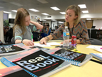 NWA Democrat-Gazette/DAVE PEROZEK<br /> English teacher Cristina Cox, right, gives seventh-grader Samantha Gower, 13, some tips on writing an essay during Thursday's (April 6, 2017) meeting of the after-school program the HUB at Lincoln Junior High School in Bentonville. The HUB, which stands for Helping Understand Better, provides students extra help in literacy and math.