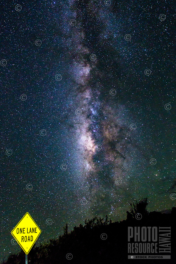 A one-land road with a yellow sign offers an incredible view of the Milky Way over Mauna Loa, Hawai'i Island.