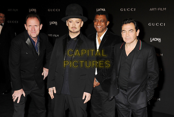 LOS ANGELES, CA - NOVEMBER 01: (L-R) Musicians Roy Hay, Boy George, wearing Gucci, Mikey Craig and Jon Moss of Culture Club attend the 2014 LACMA Art + Film Gala honoring Barbara Kruger and Quentin Tarantino presented by Gucci at LACMA on November 1, 2014 in Los Angeles, California.<br /> CAP/ROT/TM<br /> &copy;Tony Michaels/Roth Stock/Capital Pictures
