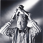 humorous photo of man, curator at Museum of Questionable Medical Devices, holding device called the Blud Rub on his head