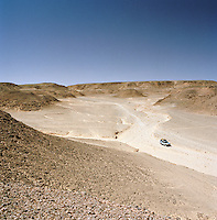 Elevated view of a 4x4 vehicle driving through a rocky part of the Sahara Desert, Libya