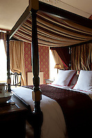 A red master bedroom with an traditional four poster bed, which dominates the room