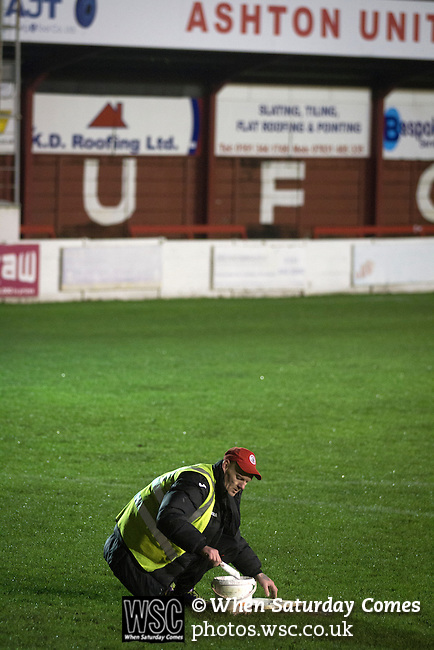 Ashton United 6 Ramsbottom United 0, 12/01/2016. Hurst Cross stadium, Northern Premier League. A groundsman painting the penalty spot before the fixture between Ashton United and Ramsbottom United in the Northern Premier League premier division. The match was played at Ashton's Hurst Cross stadium, the club's ground. The club was originally founded in 1878 as Hurst F.C. and by 1880 the club were playing at Hurst Cross, their current ground which makes their home one of the oldest football grounds in the world. Ashton won the match 6-0, watched by a crowd of 178. Photo by Colin McPherson.