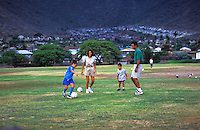 Family playing soccer in an open field in Hawaii Kai, Oahu