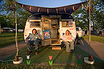 Couple sitting in front of their silver 1972 Serro Scotty Sportsman vintage travel trailer.