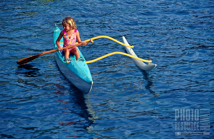 Young girl paddling in a small outrigger canoe in Kealakekua Bay on the Big Island of Hawaii.
