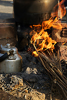 A small fire of dried grasses boils water for chai on the road in Rajasthan, India