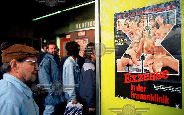 East Germans line up outside a cinema in West Berlin to get their first glimpse of Western pornography in the days after the opening of the Berlin Wall.