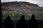 Fans watching the action from the first-half as Cambrian and Clydach Vale (in blue) take on Cwmbran Celtic at King George's New Field in a Welsh League Division One match, the top division of the Welsh Football League and the second level of the Welsh football league system. The club, formed in 1965 reached the final of the 2018-19 League Cup final and can count on ex-England manager Terry Venables as a former club chairman. Cambrian and Clydach Vale won this match 2-0, watch by a crowd of around 100 spectators.