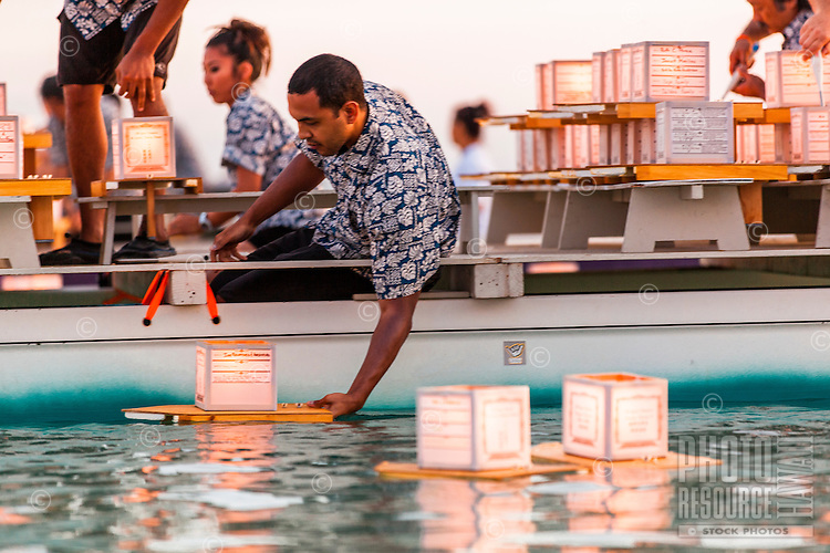 On Memorial Day, a local male volunteer on a boat places lanterns in the water at the 15th Annual Lantern Floating Ceremony at Ala Moana Beach Park, Honolulu, O'ahu.
