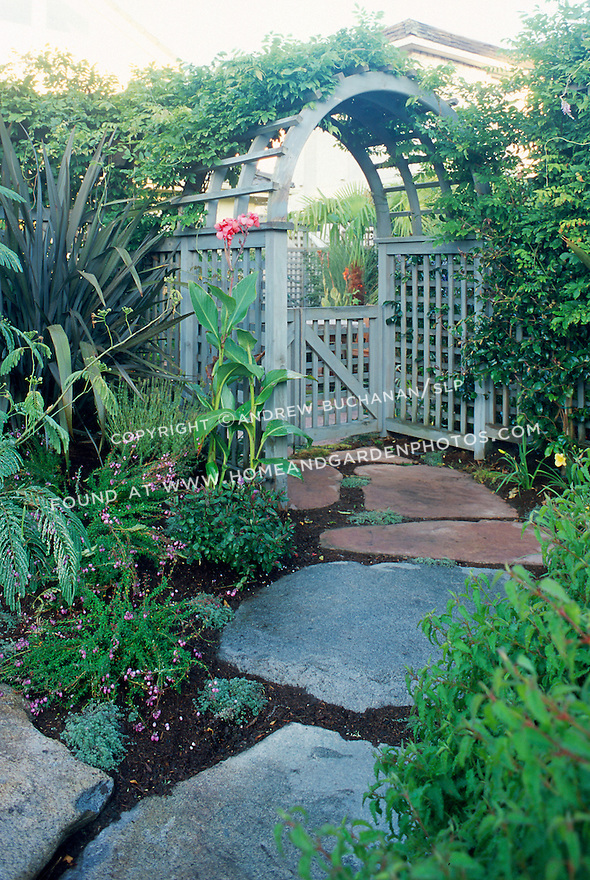Stone steps lead from the street up through an arbor gate into a hidden tropical garden.