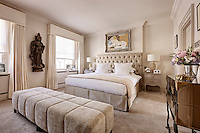 A stylish bedroom furnished in neutral tones. A double bed has an upholstered headboard and valance and the windows are dressed with matching curtains and pelmets.