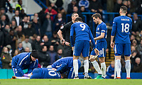 Chelsea players gather around injured Eden Hazard of Chelsea during the Premier League match between Chelsea and Tottenham Hotspur at Stamford Bridge, London, England on 1 April 2018. Photo by Andy Rowland.