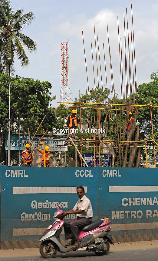 A man on the mopet is passing in front of the building construction site in Madras, India.