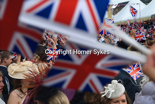 Ascot Horse Racing Berkshire Uk. Racegoers wave the Union Jack flag while singing Land of Hope and Glory around the band stand at the end of the days racing. 2012
