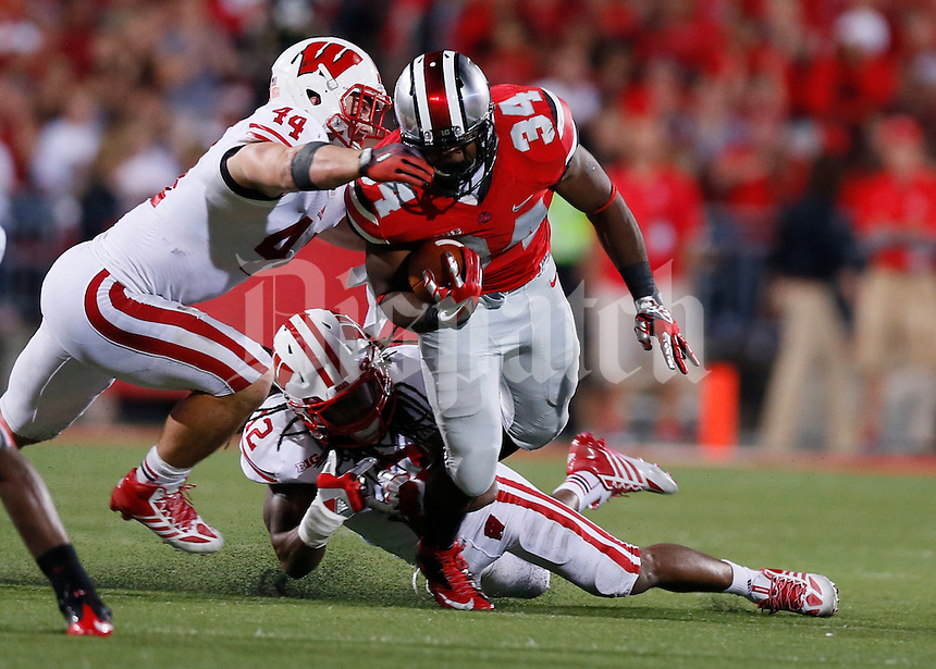 Ohio State Buckeyes running back Carlos Hyde (34) is tackled by Wisconsin Badgers linebacker Chris Borland (44) and Wisconsin Badgers safety Dezmen Southward (12) during Saturday's NCAA Division I football game at Ohio Stadium in Columbus on September 28, 2013. (Barbara J. Perenic/Columbus Dispatch)