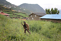 A man walks through a village in the Tibetan foothills near the town of Heishui on the south-east edge of the Tibetan Plateau in Sichuan Province, western China.