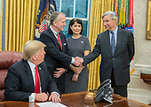 "United States Senator Dan Sullivan (Republican of Alaska), center left, shakes hands with US Senator Sheldon Whitehouse (Democrat of Rhode Island), right, as US President Donald J. Trump, left, and Julie Fate, wife of Senator Sullivan, center right, look on as the President makes remarks prior to signing S. 3508, the ""Save Our Seas Act of 2018"" in the Oval Office of the White House in Washington, DC on Thursday, October 11, 2018.  <br /> Credit: Ron Sachs / CNP"