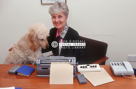 Woman with visual impairment sitting at desk in front of Braille typewriter stroking guide dog,