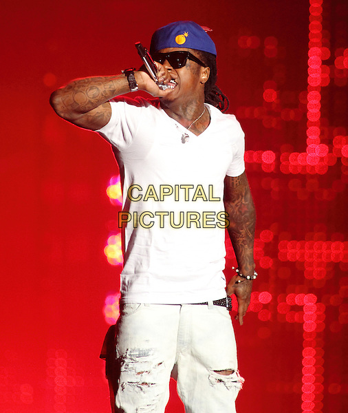 LIL' WAYNE (Dwayne Michael Carter, Jr.).Lil' Wayne performs on his I'm Still Music Tour 2011 at the 1st Mariner Arena in Baltimore, Md, USA..March 20th, 2011 .stage concert live gig performance music half length white t-shirt blue baseball cap hat microphone tattoos singing .CAP/RKE/EML.©EML/RockinExposures/Capital Pictures.