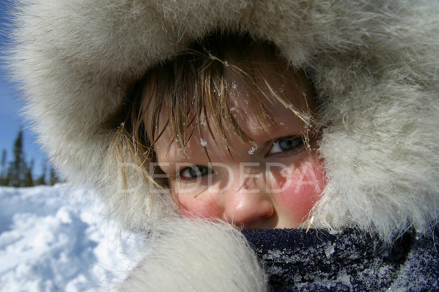 Nora, dressed in her winter jacket, stands outside in the remote Arctic village of Old Crow, Yukon Territory, Canada.