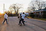 "Kevin ""Booma"" Williams (black shirt), 18, plays Ta Posey (white shirt), 18, in a game of street basketball while Leandrew Myers, 15, looks on on Kilpatrick Street in Greensboro, Alabama, February 28, 2013, where over a quarter of the population receives Social Security Disability benefits."