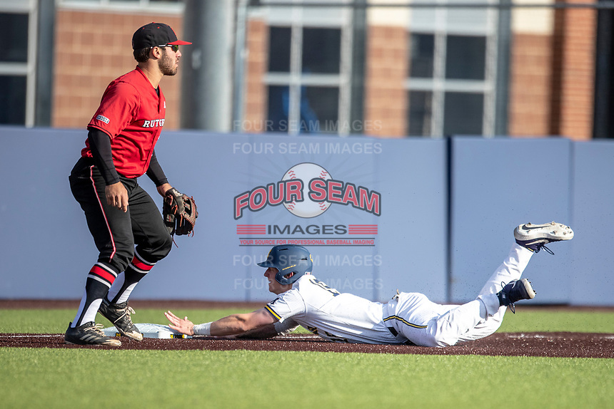Michigan Wolverines first baseman Jimmy Kerr (15) slides head first into third base as Rutgers Scarlet Knights third baseman Carmen Sclafani (19) waits for a throw on April 26, 2019 in the NCAA baseball game at Ray Fisher Stadium in Ann Arbor, Michigan. Michigan defeated Rutgers 8-3. (Andrew Woolley/Four Seam Images)