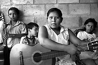 Young woman and students preparing for a music lesson.<br /> Part of the 'Music for Hope' project.<br /> Nueva Esperanza, Bajo Lempa, El Salvador, August 1999.