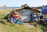 Old upturned boat used as store shed for fishing equipment, Holy Island, Lindisfarne, Northumberland, England, UK
