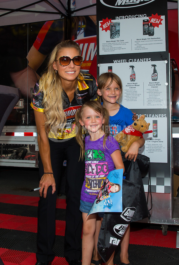 Jun 19, 2015; Bristol, TN, USA; NHRA top fuel driver Leah Pritchett poses with a couple young female fans during qualifying for the Thunder Valley Nationals at Bristol Dragway. Mandatory Credit: Mark J. Rebilas-