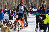 Alex Buetow and team run past spectators on the bike/ski trail during the Anchorage ceremonial start during the 2014 Iditarod race.<br /> Photo by Britt Coon/IditarodPhotos.com