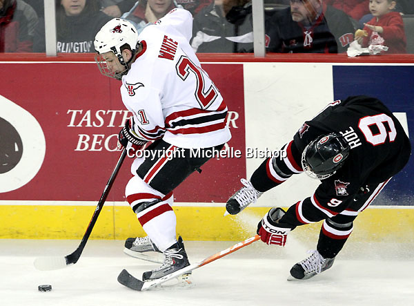 UNO's Matt White works the puck past St. Cloud State's Garrett Roe. UNO beat St. Cloud State 3-0 Friday night at Qwest Center Omaha.  (Photo by Michelle Bishop)