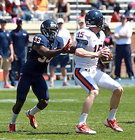 Virginia quarterback Matt Johns (15) is sacked by Virginia cornerback Kirk Garner (33) during the annual Virginia football Orange-Blue Spring Game Saturday at Scott Stadium in Charlottesville, VA. Photo/The Daily Progress/Andrew Shurtleff