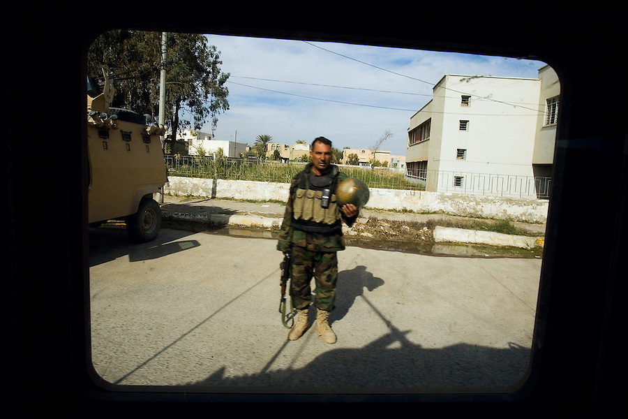 Viewed through the armored window of a passing Humvee, an Iraqi soldier stands at a checkpoint in the Diyala Province, Baqubah on Mon. Dec. 4, 2006.<br />