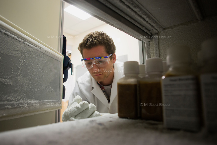 Mark Smith is a PhD candidate in MIT's Microbiology Graduate Program and helps run the OpenBiome project at MIT in Cambridge, Massachusetts, USA.  Fecal microbiota preparations, from donated fecal material, stand in bottles in a freezer at about -80 degrees F in a laboratory used by the OpenBiome project in MIT's Microbiology Program in Cambridge, Massachusetts, USA.  The OpenBiome project screens donations for a variety of disease agents and then provides these samples to hospitals around the US for treatment of clostridium difficile infection, which affects approximately 500,000 people in the US and kills about 14,000 annually. The samples are used in fecal microbiotal transplants (fecal transplants) and work as extremely efficient treatment for c. difficile infections.