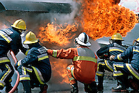 Firefighters attacking a fire aboard an aircraft. They are crouched down for safety where the temprature is not so high and are using pulses of water to extinguish the fire and to act as a barrier between them and the heat and flames. The firefighter in the orange tunic is the officer in charge of this crew...© SHOUT. THIS PICTURE MUST ONLY BE USED TO ILLUSTRATE THE EMERGENCY SERVICES IN A POSITIVE MANNER. CONTACT JOHN CALLAN. Exact date unknown.john@shoutpictures.com.www.shoutpictures.com..