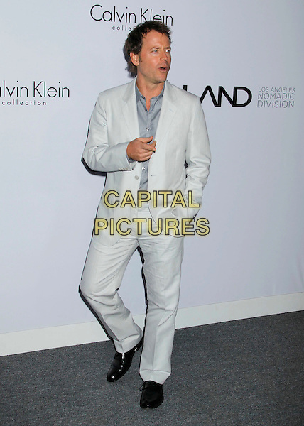 GREG KINNEAR .Attending Calvin Klein Collection and LOS ANGELES NOMADIC DIVISION present a celebration of L.A. Arts Month held at the Calvin Klein Store, Los Angeles, CA, USA, 28th January 2010..full length white grey gray suit shirt hand in pocket finger gesture .CAP/ADM/MJ.©Michael Jade/Admedia/Capital Pictures